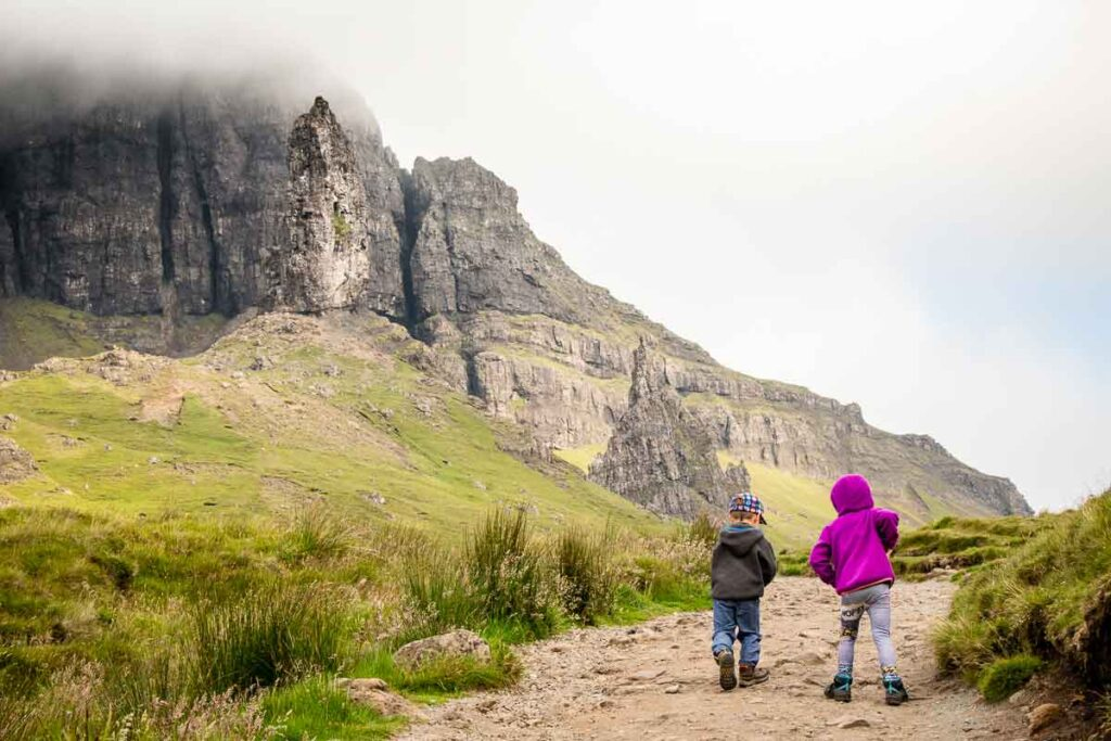 image of two kids walking side by side on the Old Man of Storr Hike Isle of Skye Scotland