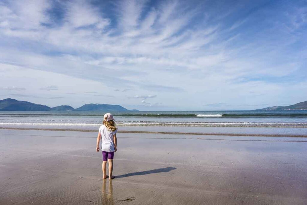 image of girl standing looking at the water on Inch Beach on the Dingle Peninsula Ireland