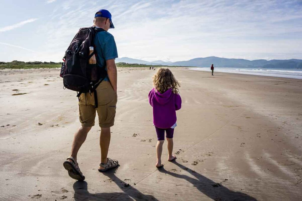 image of father and daughter walking along Inch Beach on Dingle Peninsula Ireland