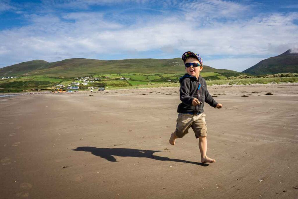 image of boy in sunglasses, cap and grey hoodie running along Inch Beach with green hills in background in Ireland