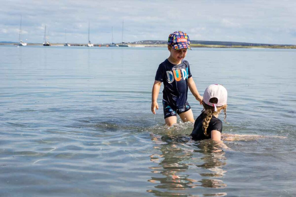image of two kids in tshirts and caps playing in the ocean on Inis Mor Aran Island in Ireland
