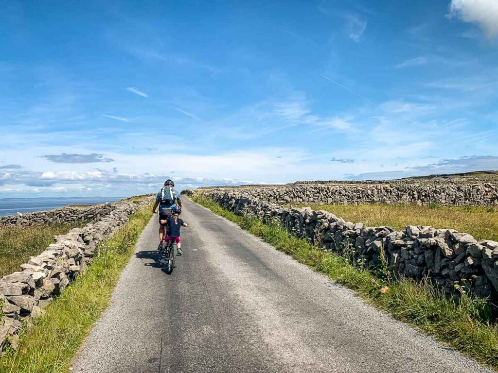image of man on cycle with girl on tag-a-long bike cycling on Aran Island Inishmore with kids