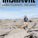 image of boy walking across large grey rocks with text overlay of Inishmore Aran Islands Ireland