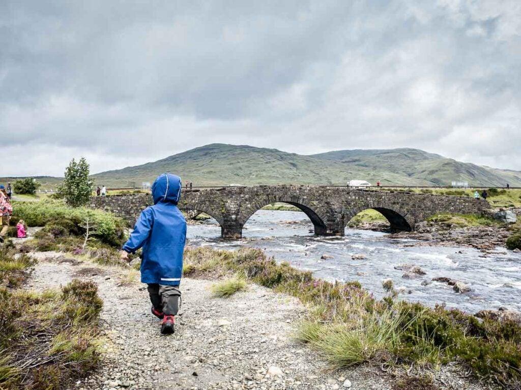 image of boy in blue rain jacket walking towards bridge on Isle of Skye