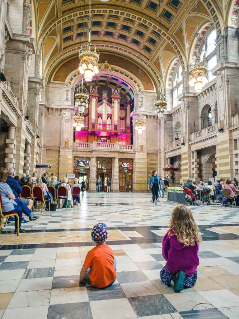 Image of kids sitting on floor listening to organ recital at Kelvingrove Art Gallery and Museum in Glasgow Scotland