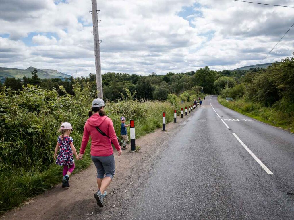 image of mother and two kids walking along highway in Scotland towards entry to Devils pulpit