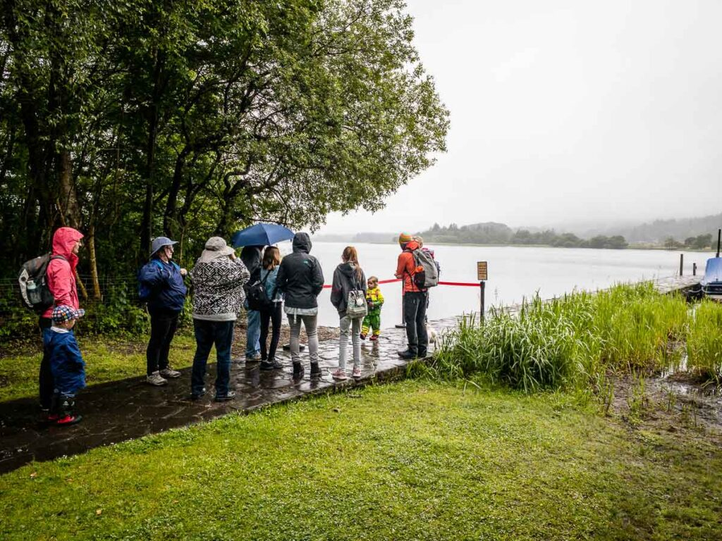 image of people waiting in line for boat ride from Port of Menteith to island with Inchmahone Priory