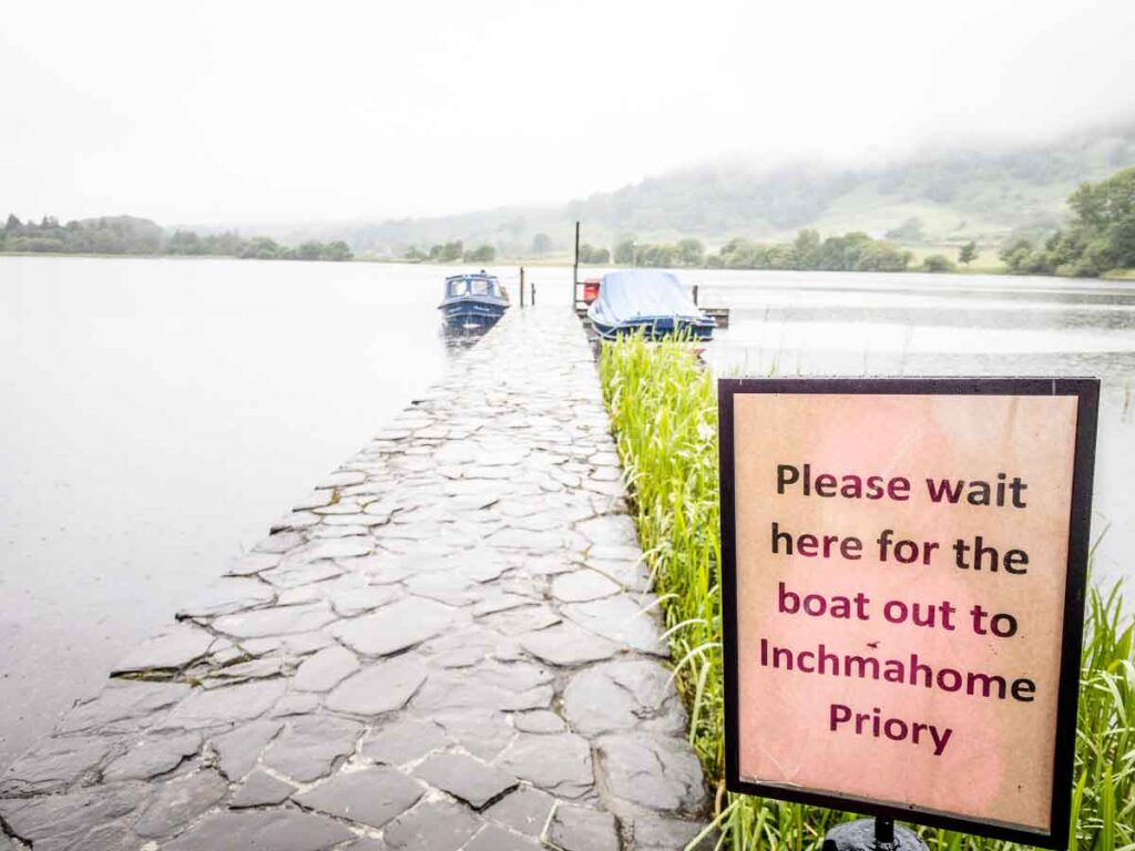 "image of sign saying ""please wait here for the boat out to Inchmahome Priory"""