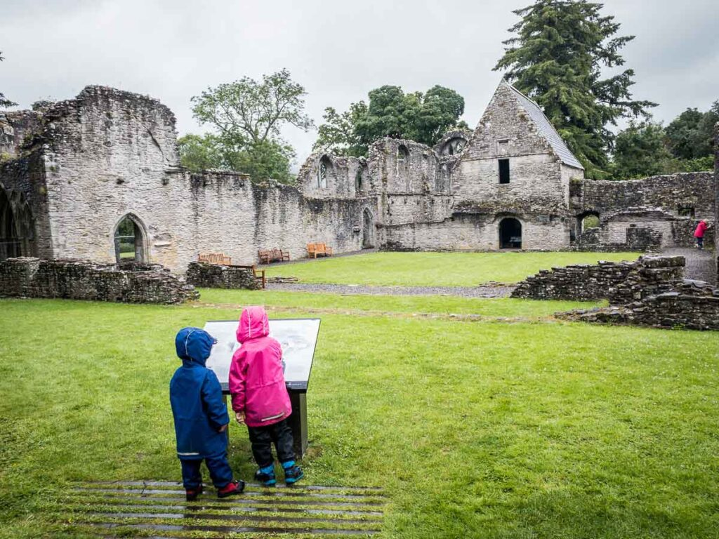 image of two kids in rain jackets looking at Inchmahome Priory in Scotland