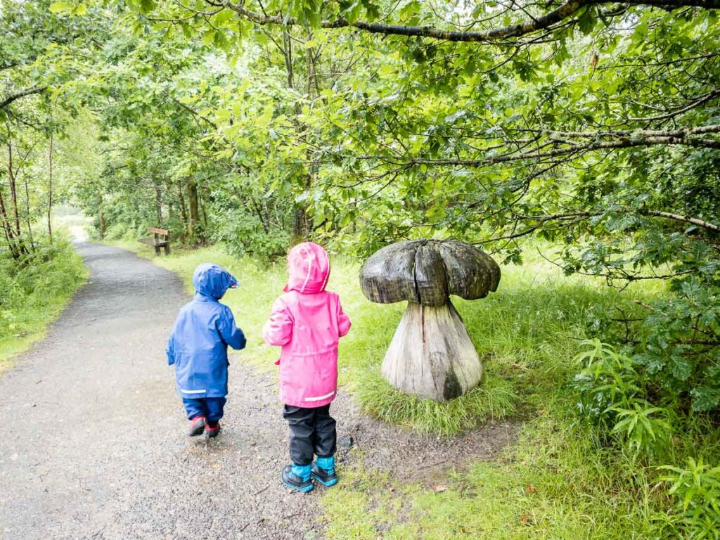 image of two kids in rain jackets near a wooden mushroom along interactive waterfall trail inQueen Elizabeth Forest Park Trossachs National Park Scotland