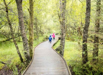 image of two kids in rain jackets running on wooden boardwalk in Queen Elizabeth Forest Park Scotland