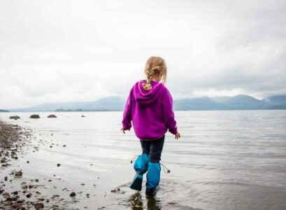 image of girl in purple hoodie and blue rain boots standing in Loch Lomond in Scotland