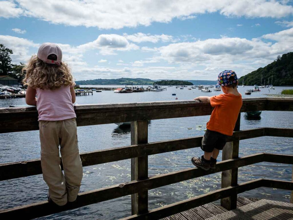 image of two kids standing on wooden railing overlooking Loch Lomond