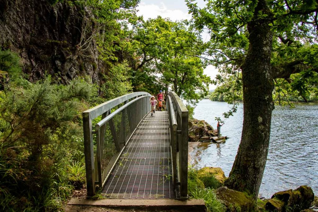 image of man and two kids walking along metal footbridge along the shores of Loch Lomond
