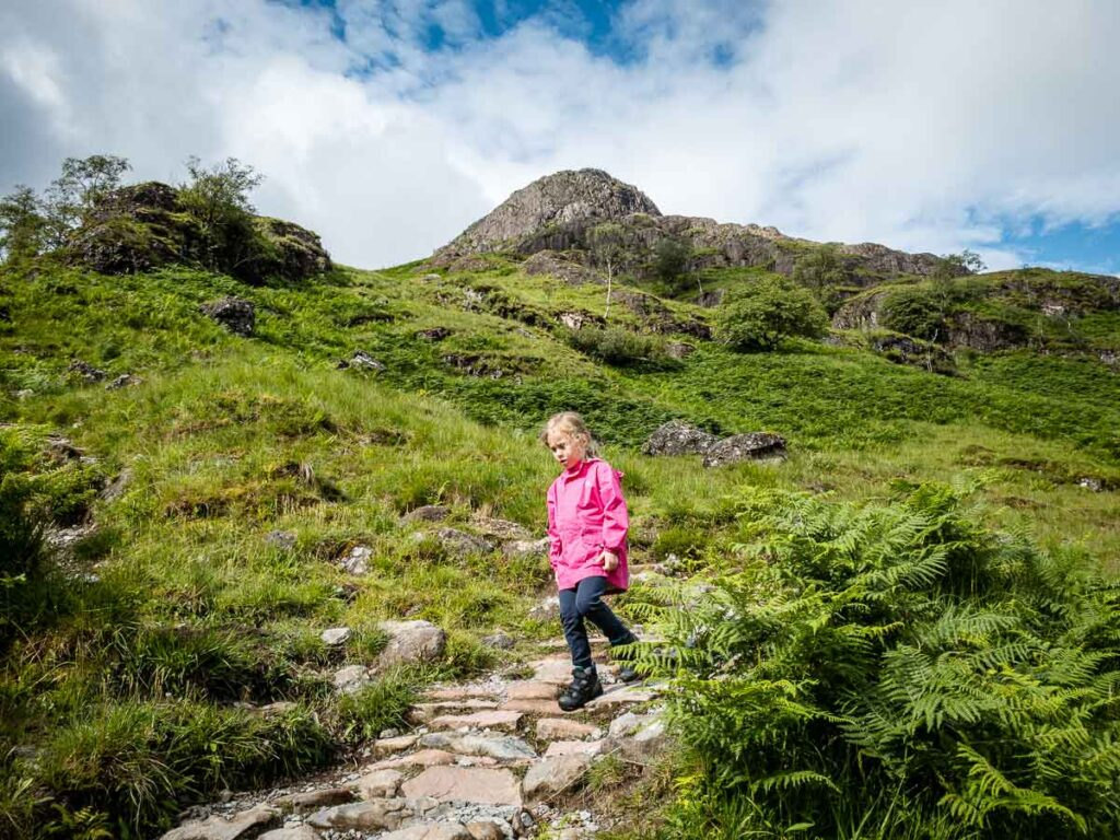 image of girl walking down rock steps while hiking in Glencoe Scotland