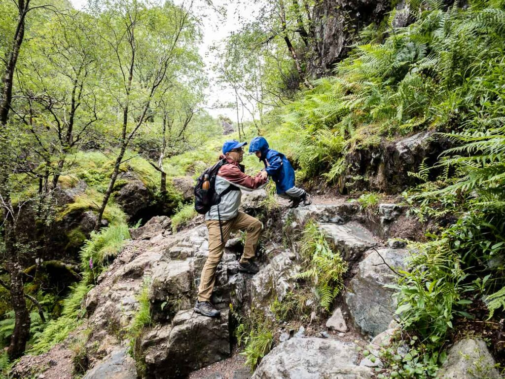 image of boy jumping off rock into father's arms on Lost Valley Hike in Glencoe Scotland