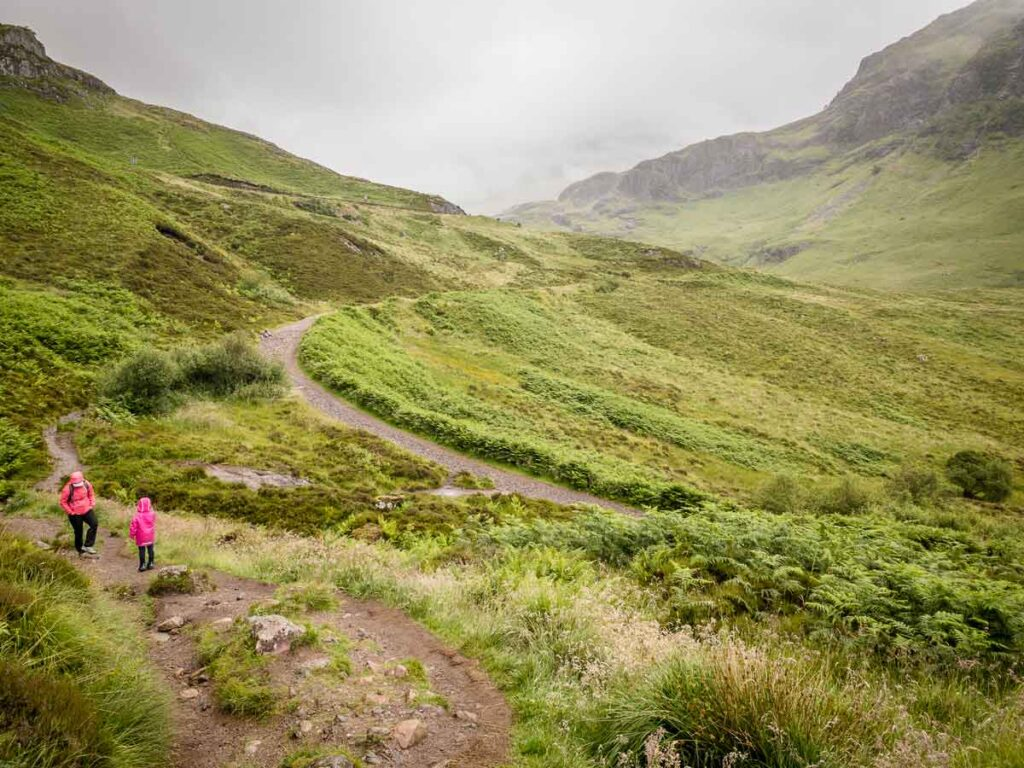 image of mother and girl both in pink rain jackets hiking in Glencoe Scotland surrounded by lush green mountains