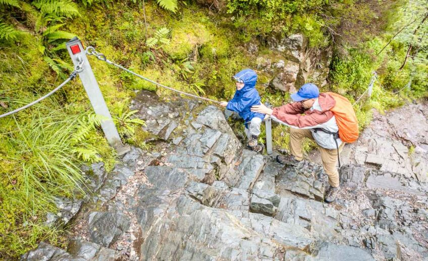 image of boy in blue rain jacket climbing up rocks using rope with help from father along Lost Valley Trail in Glencoe Scotland