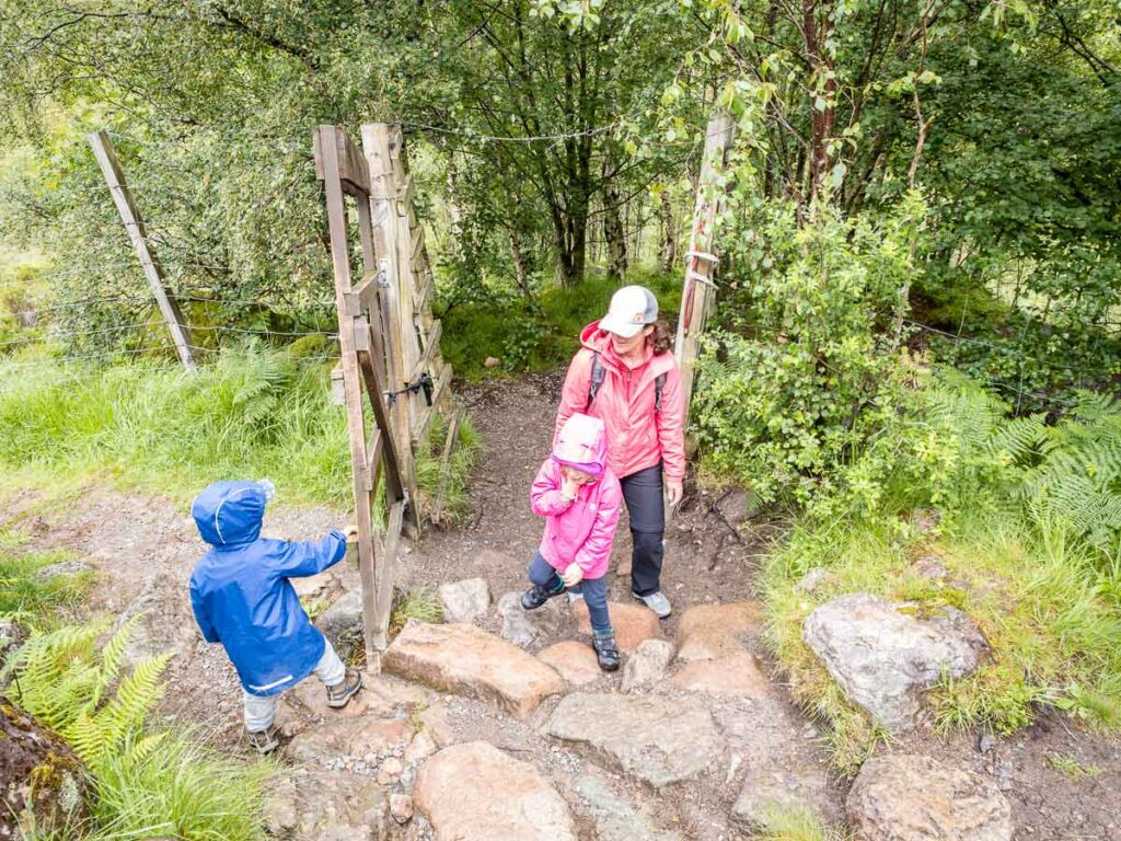 Image of boy holding gate open for mother and girl along one of the best walks in Glencoe with kids