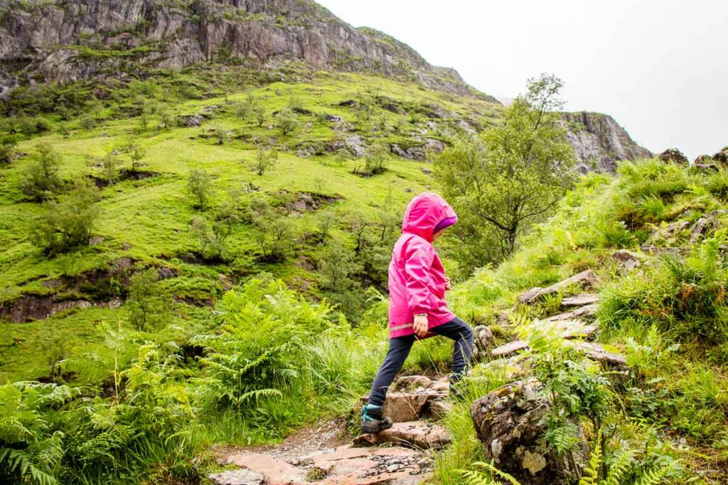 image of girl in pink rain jacket hiking up rocks along Lost Valley Hiking Trail in Glencoe Scotland