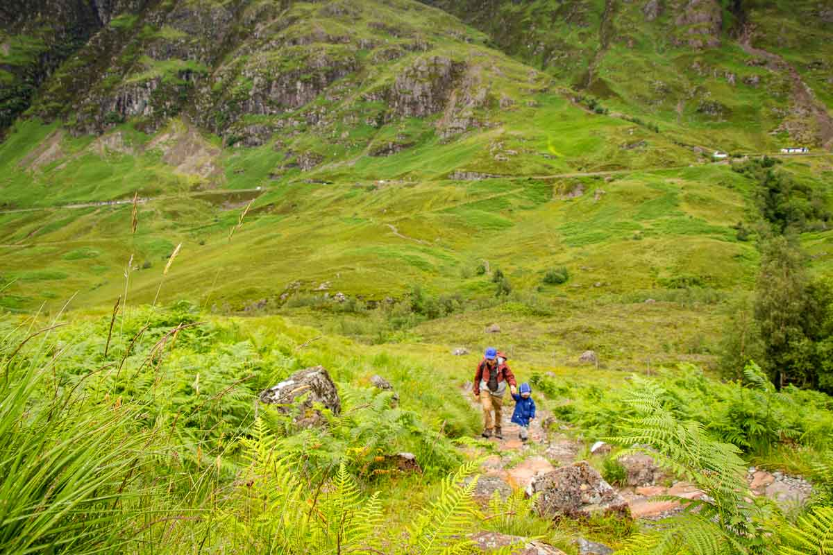 image of father holding boys hand hiking up mountain with highway and carpark in Glencoe Scotland