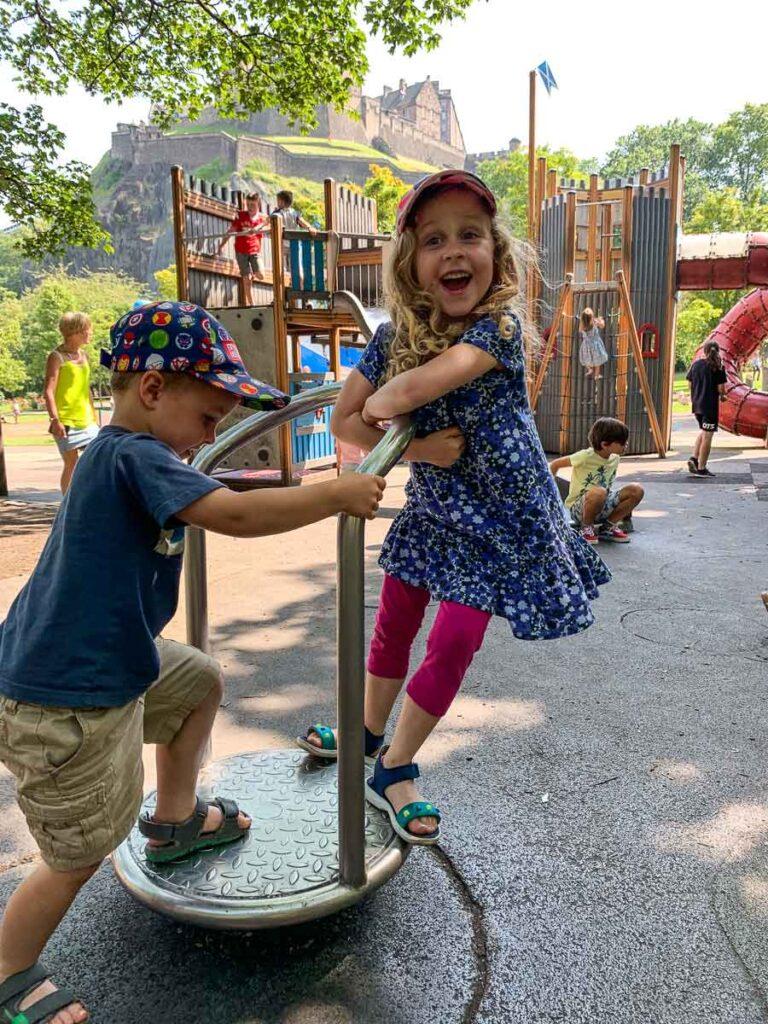 Image of children smiling on playground in Princes Street Gardens in Edinburgh Scotland
