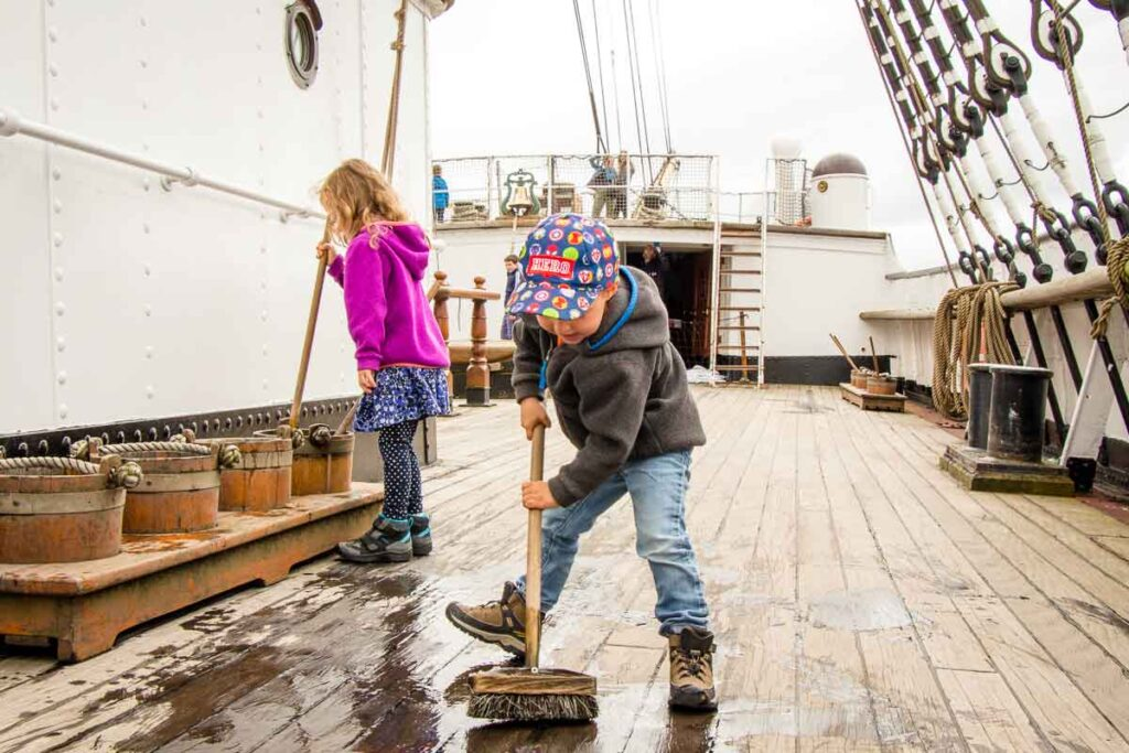 image of kids cleaning the floor of the Glenlee Tall Ship at Riverside Museum in Glasgow Scotland