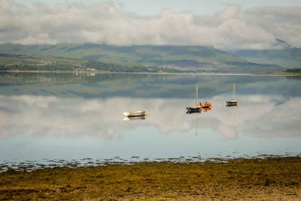 image of lake with 4 small boats in Scotland