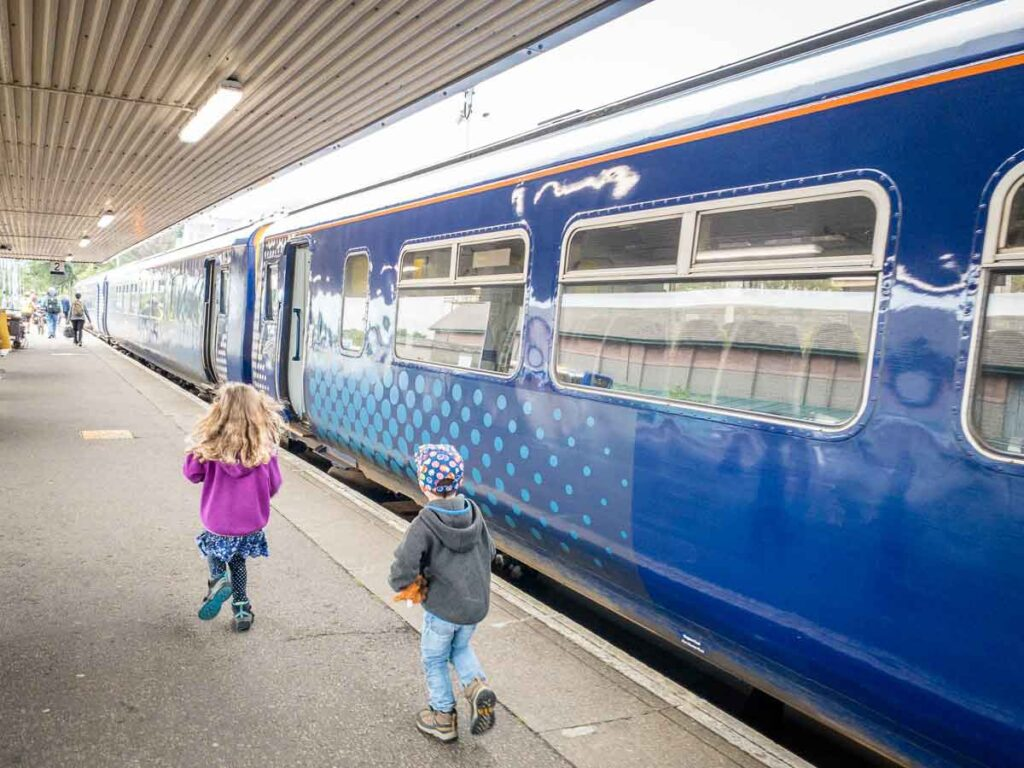image of kids running towards Scotrail train that goes from Fort William to Mallaig over the Glenfinnan Viaduct