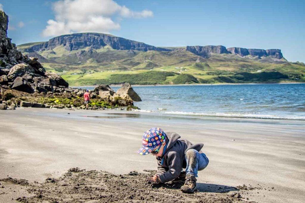 image of boy in grey hoodie and cap playing on Slipaway Beach on Isle of Skye