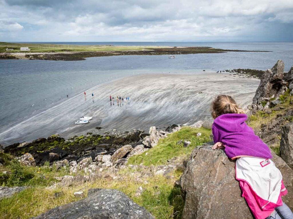 image of girl in purple hoodie looking down on Slipaway Beach