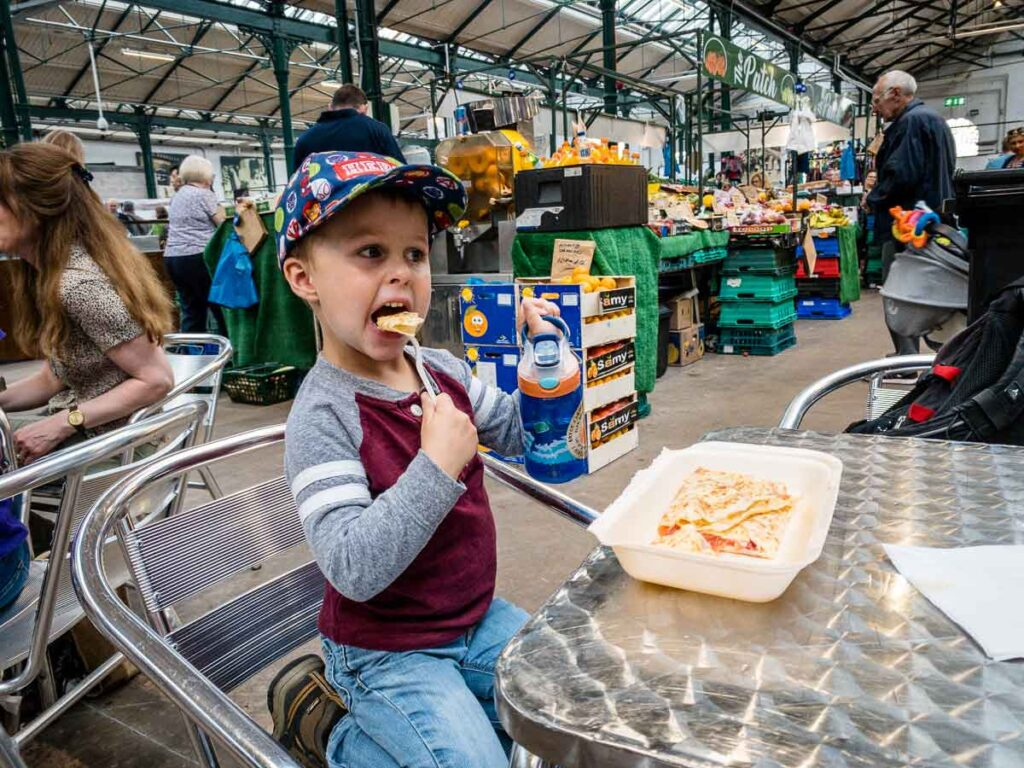 Image of boy sitting at table eating in St George's Market in Belfast