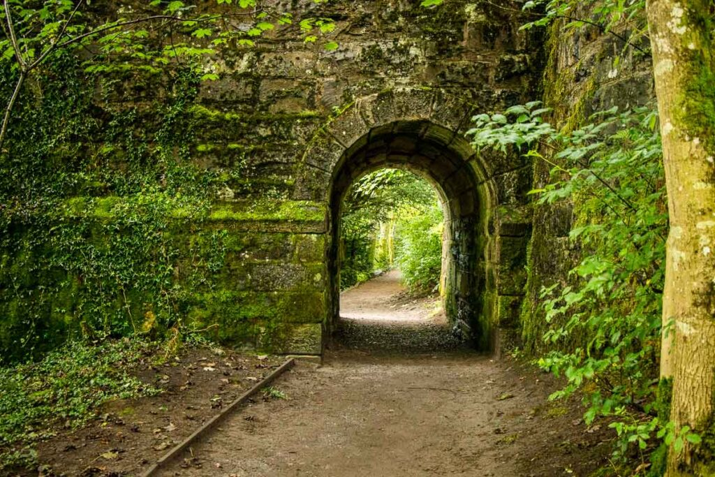 Image of stone wall with archway along one of the Tay Forest Park Walks in Scotland (near Pitlochry)