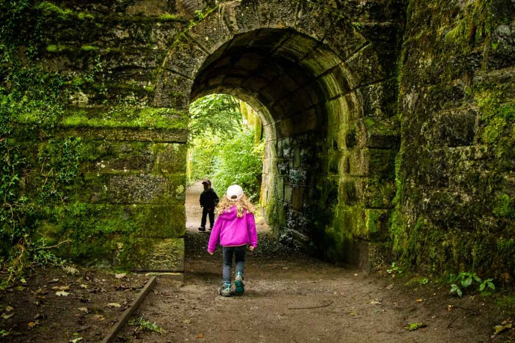 Image of kids running through stone arch in Tay Forest Park