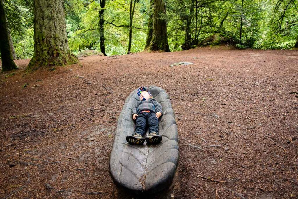 image of boy on a carved wooden sculpture in Tay Forest Park near Pitlochry Scotland