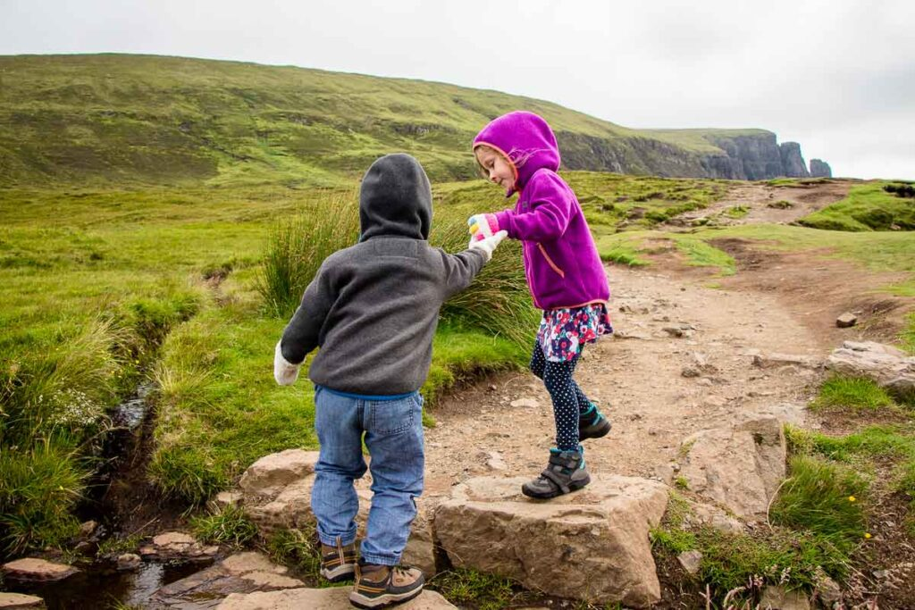 image of girl in purple hoodie helping her brother over rocks while hiking the Quiraing on Isle of Skye with kids