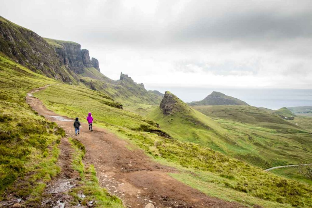 image of boy and girl hiking side by side on the Quiraing hike on Isle of Skye