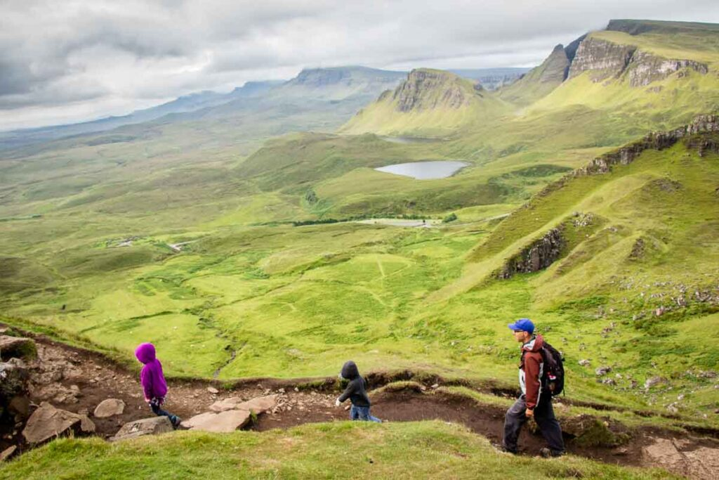 image looking down on quiraing hiking trail with lake and mountains on Isle of Skye