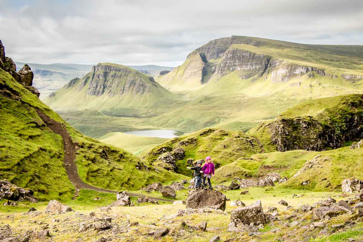 image of boy and girl standing on rock with incredible views from Quiraing hike in the background