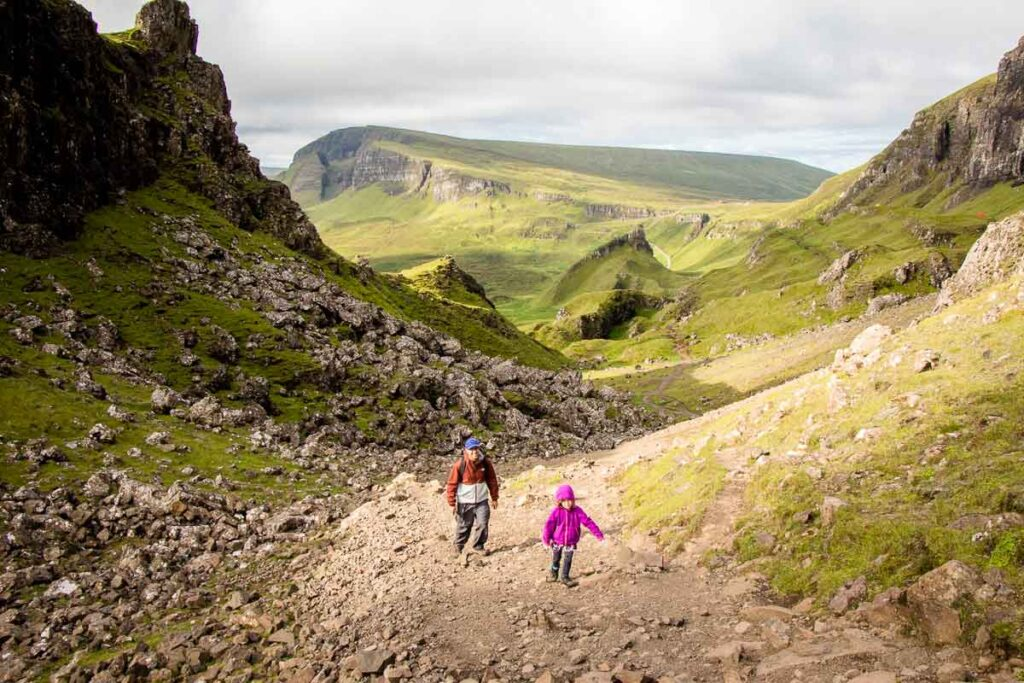 image of father and daughter hiking up a steep rocky trail on Quiraing hike on Isle of Skye