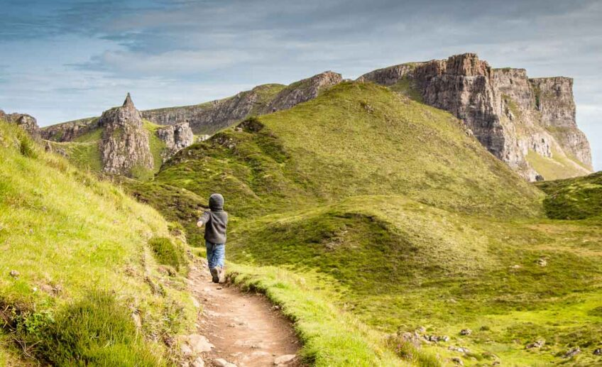 image of boy hiking on trail with rocky cliffs and green hills in the distance