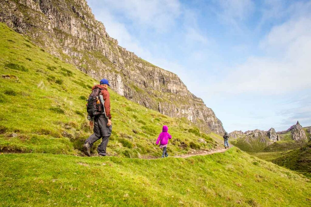 image of father and two kids hiking along the Quiraing hike with rocky cliffs along one side