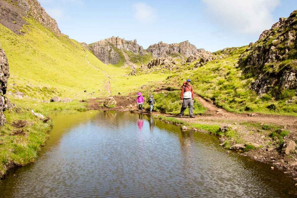 image of father and two kids walking by a pond with mountains in the background on Isle of Skye Quiraing Hike