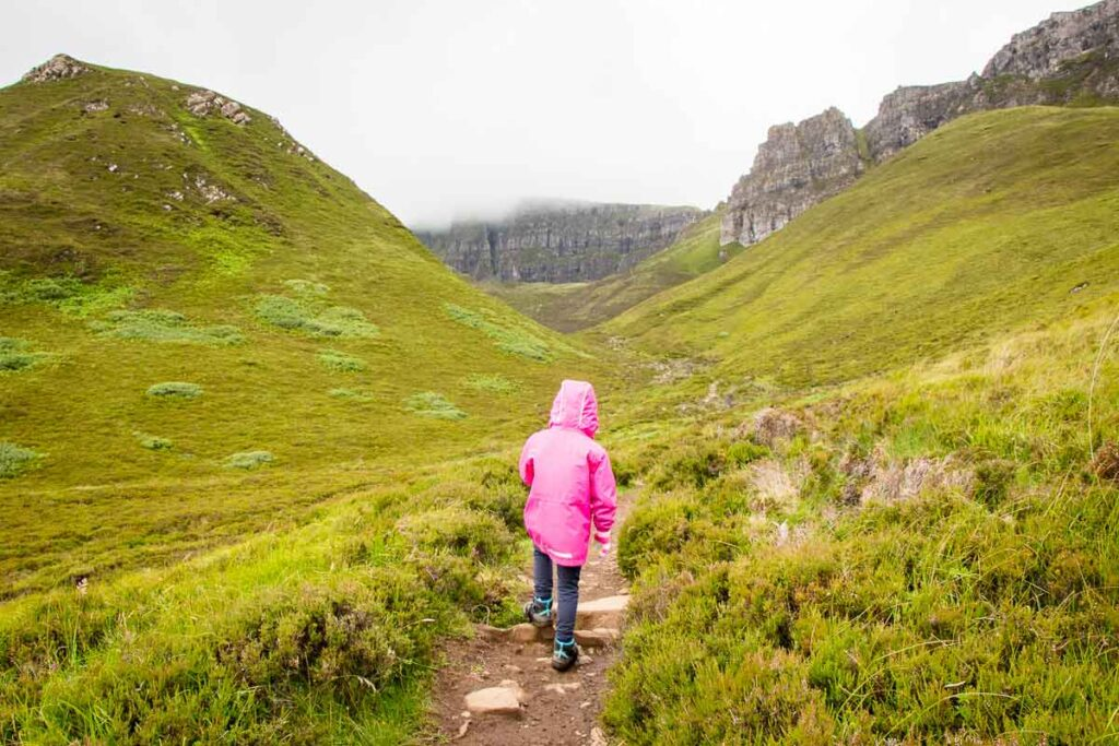 Image of girl in pink rain jacket hiking up towards rocky mountains