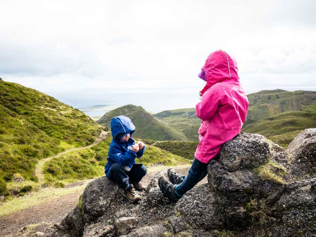 image of kids having a snack on rock with mountains and ocean in the distance on Isle of Skye