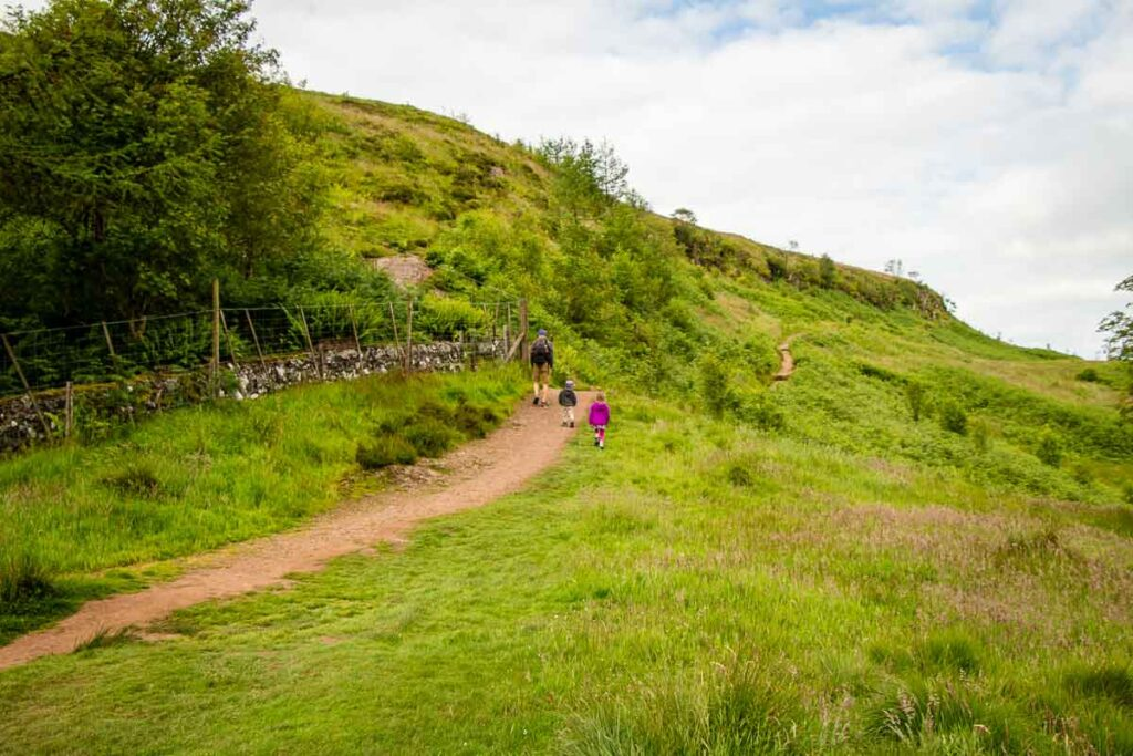 image of father with two kids walking along the Whangie hike from the Queensview car park