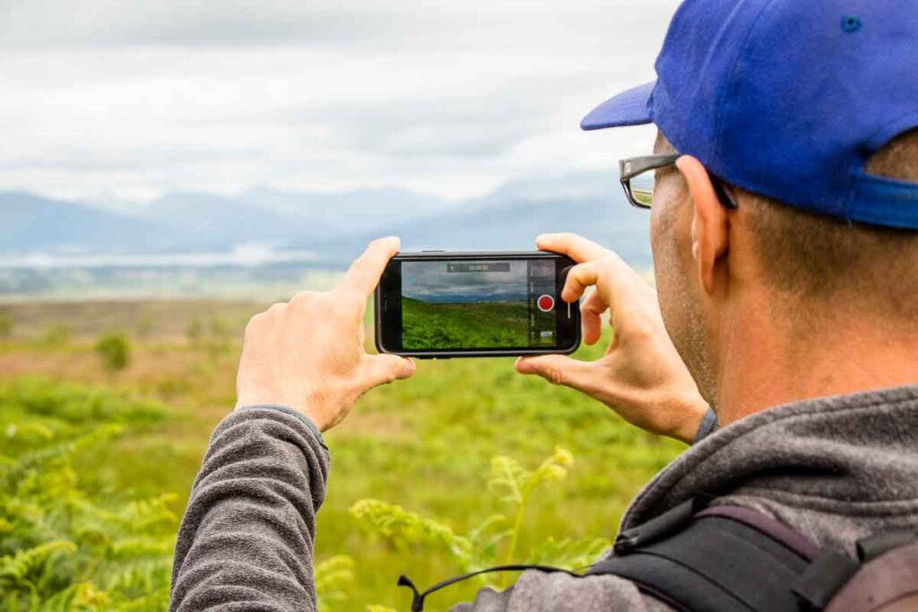 image of man taking a picture of phone of loch lomond from the Whangie hill walk in Scotland