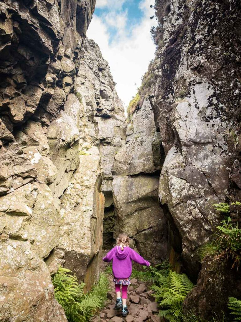 image of girl in purple hoodie walking a narrow path between two rock walls while hiking in Scotland
