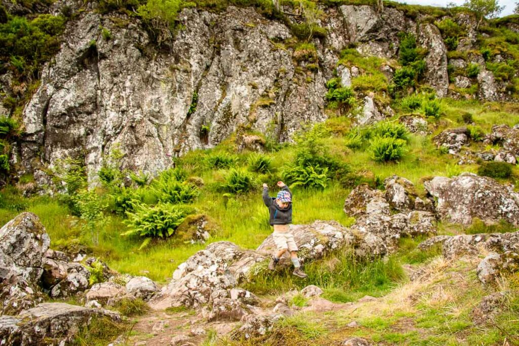 Image of boy jumping off a rock along the Whangie hiking trail in Scotland