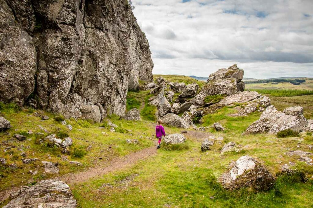 image of girl in purple hoodie walking to the Whangie in Scotland